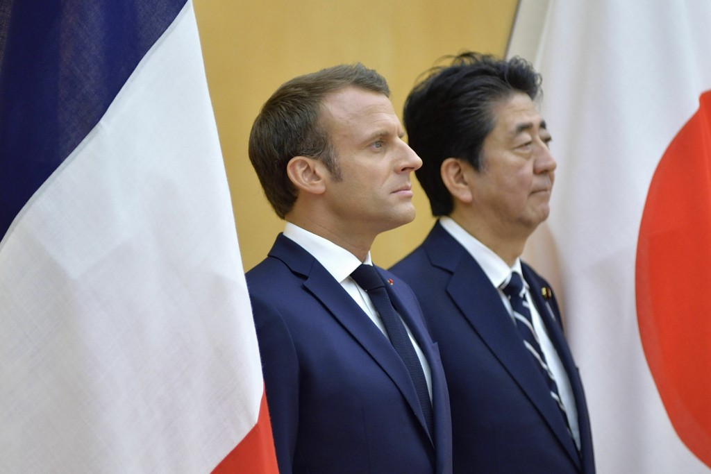 French President Emmanuel Macron, left, and Japanese Prime Minister Shinzo Abe review an honor guard prior to their meeting at Abe's official residenc...