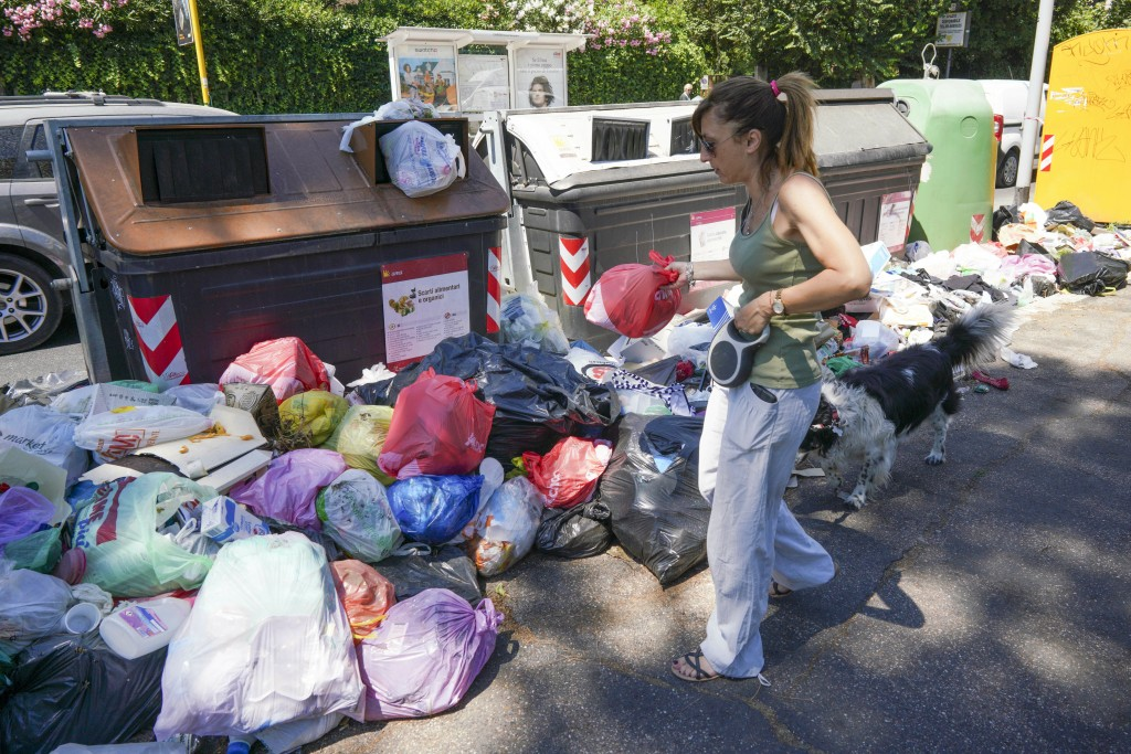 In this photo taken on Monday, June 24, 2019, a woman walks by uncollected garbage, in Rome. Doctors in Rome are warning of possible health hazards ca...