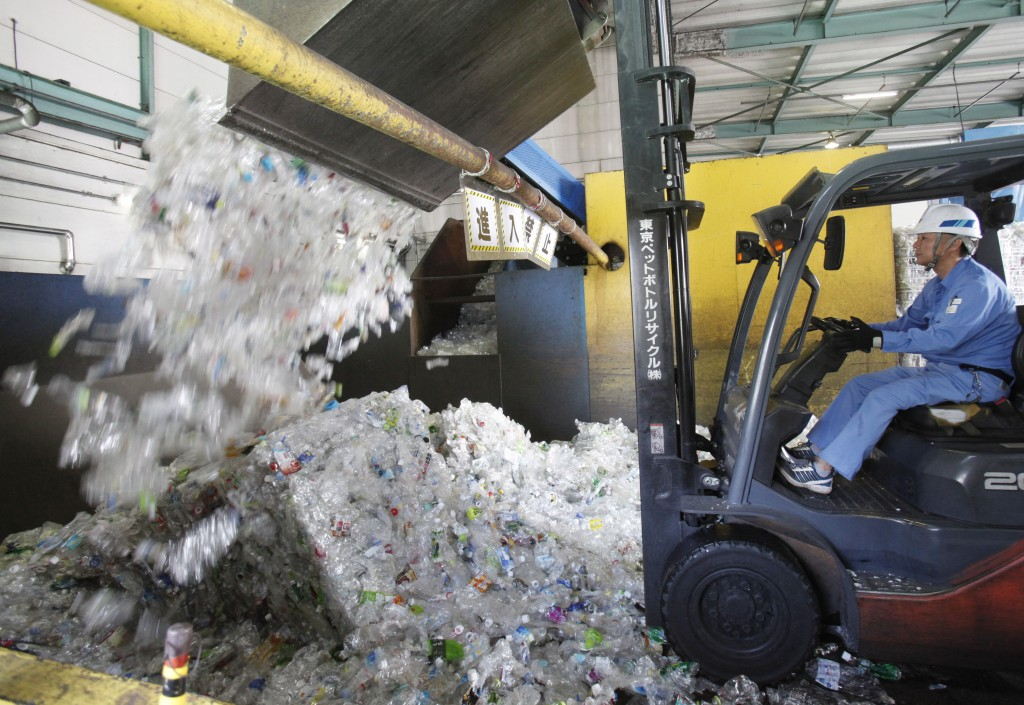 In this June 18, 2019, photo, a plastic recycling company worker adds used plastic bottles into bale breaker for processing, at Tokyo Petbottle Recycl