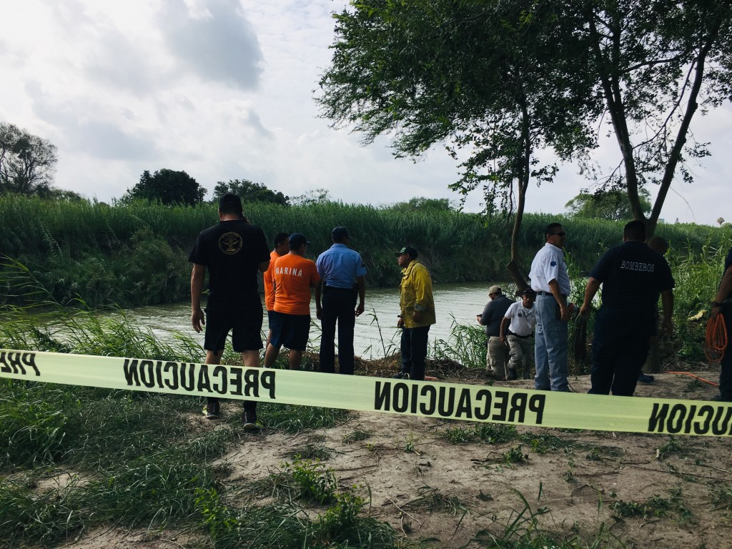 Authorities stand behind yellow warning tape along the Rio Grande bank where the bodies of Salvadoran migrant Oscar Alberto Martínez Ramírez and his n...