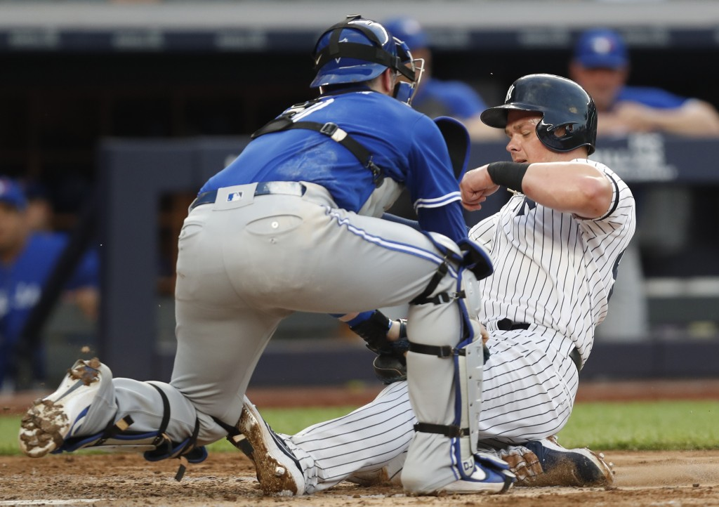 Toronto Blue Jays' catcher Danny Jansen, left, tags out New York Yankees' Luke Voit at the plate during the fourth inning of a baseball game Tuesday, ...