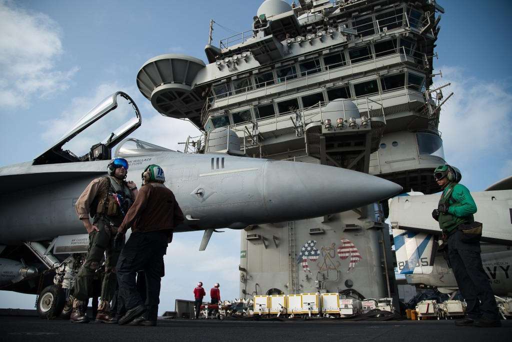 FILE - In this June 3, 2019 file photo, a pilot speaks to a crew member by an F/A-18 fighter jet on the deck of the USS Abraham Lincoln aircraft carri...