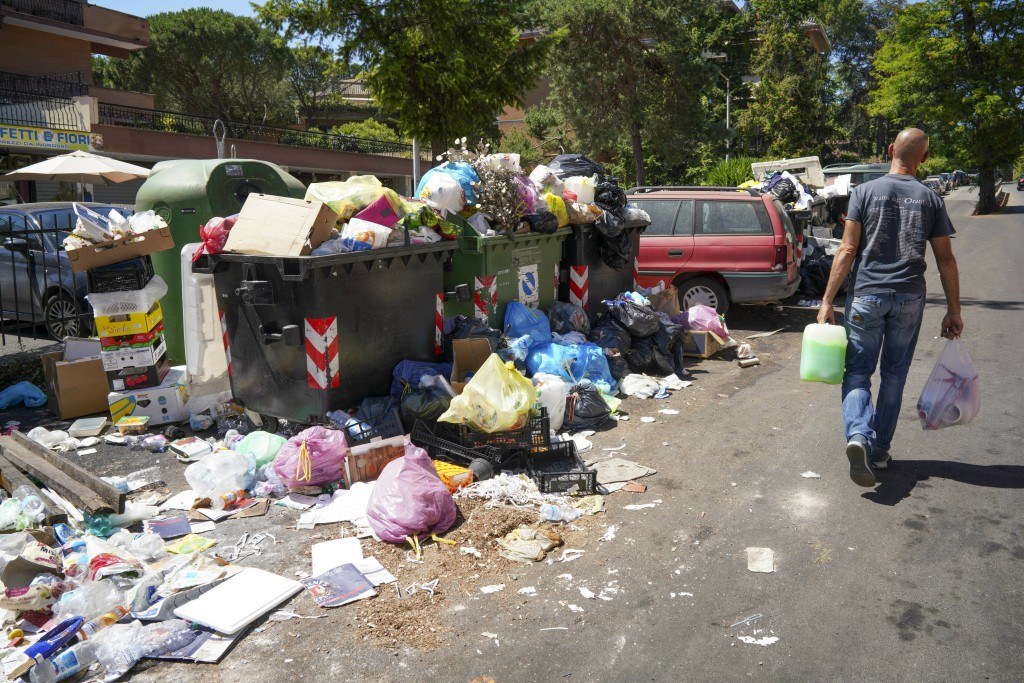 In this photo taken on Monday, June 24, 2019, a man walks past a pile of garbage in Rome. Doctors in Rome are warning of possible health hazards cause...