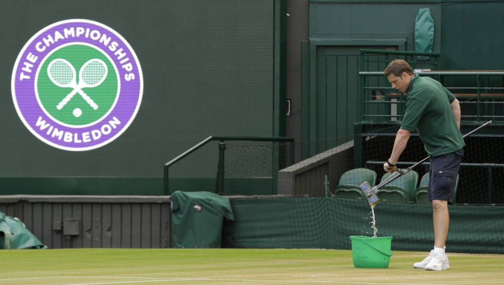FILE - In this July 13, 2017, file photo, Ben Sidgwick wrings out his mop on Center Court at the All England Club at the Wimbledon Tennis Championship...
