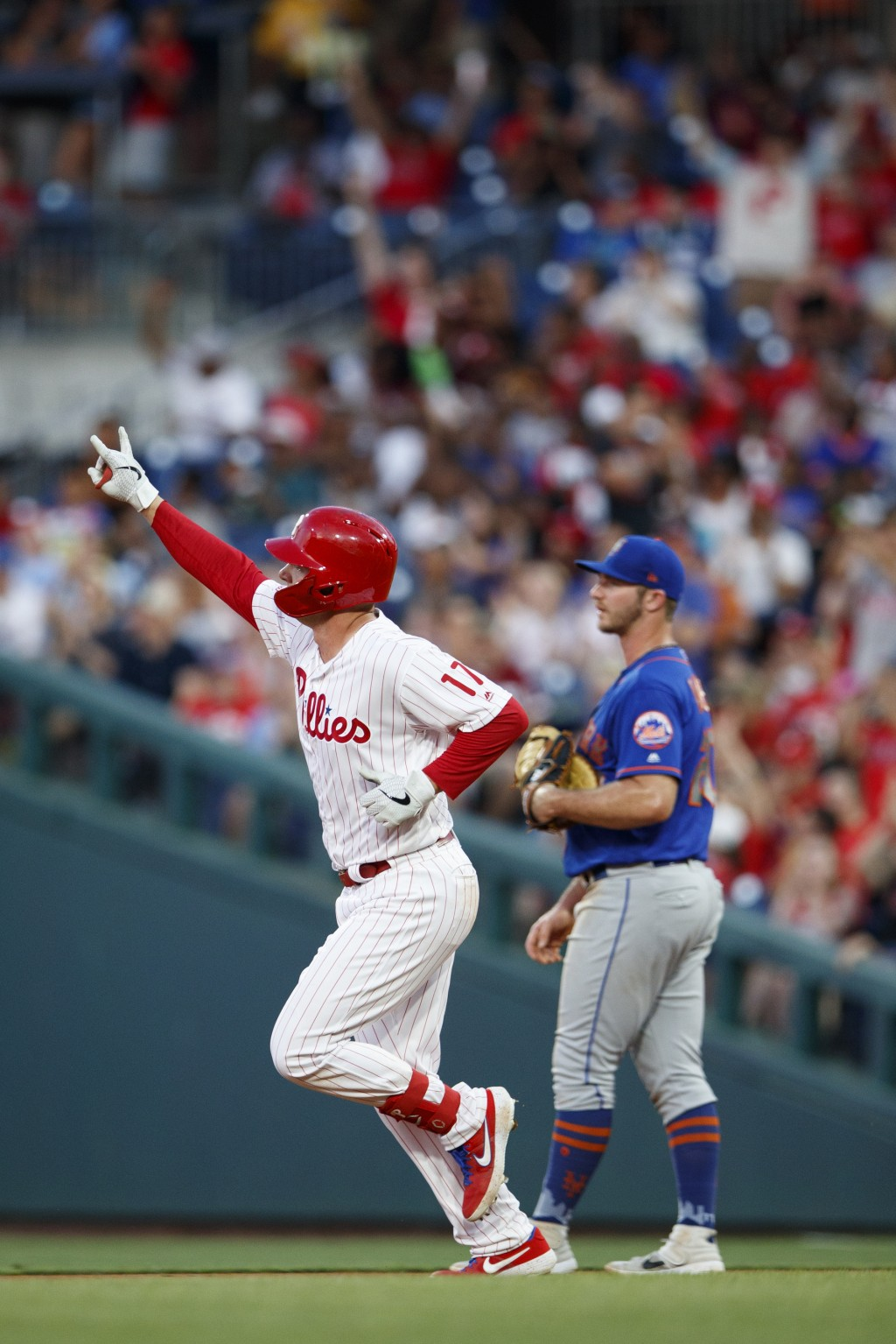 Philadelphia Phillies' Rhys Hoskins, left, reacts as he runs the bases past New York Mets first baseman Pete Alonso after hitting a home run off start...