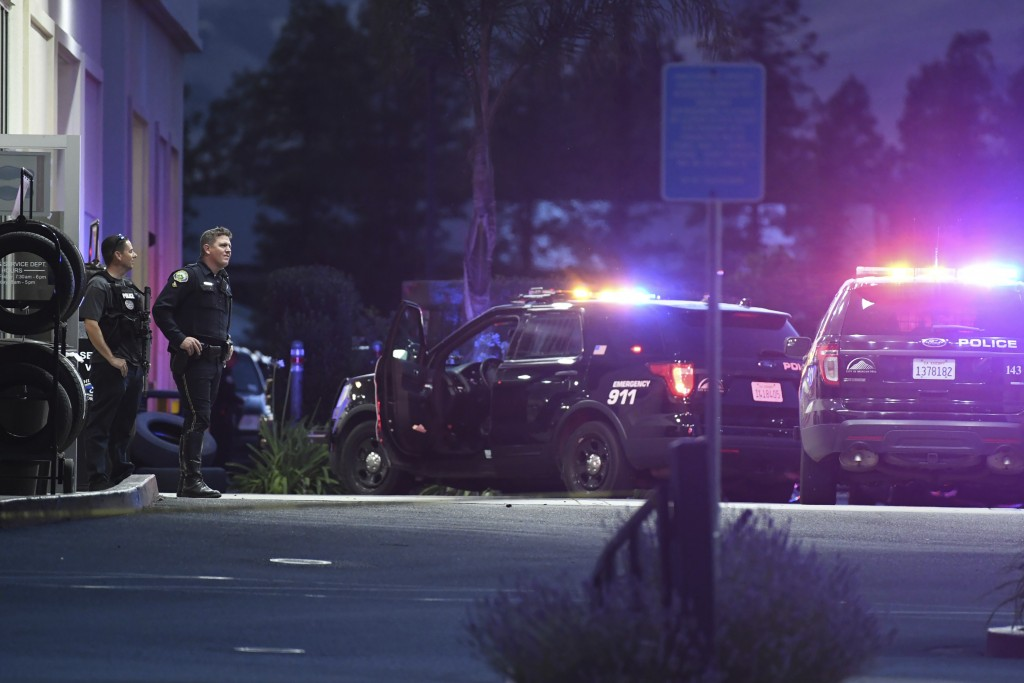 Law enforcement officers stand outside a building at a Ford dealership after a fatal shooting Tuesday, June 25, 2019, in Morgan Hill, Calif. A man who...