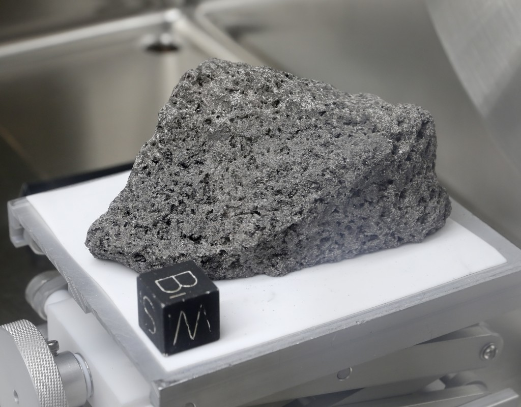 "Collected during Apollo 17, a 3.5 billion year old basalt rock known as ""The Children of the World"" or ""The Goodwill Sample"" is displayed in the lunar..."