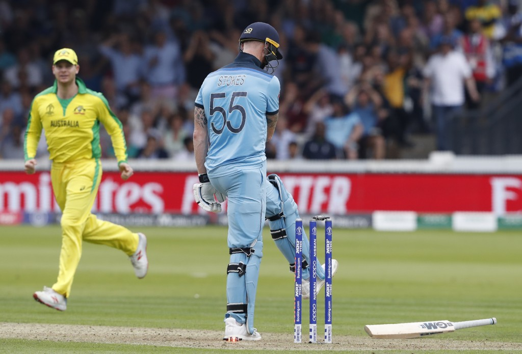 England's Ben Stokes kicks his bat after being clean bowled by Australia's Mitchell Starc, as Australia's Steve Smith looks on during the Cricket Worl...