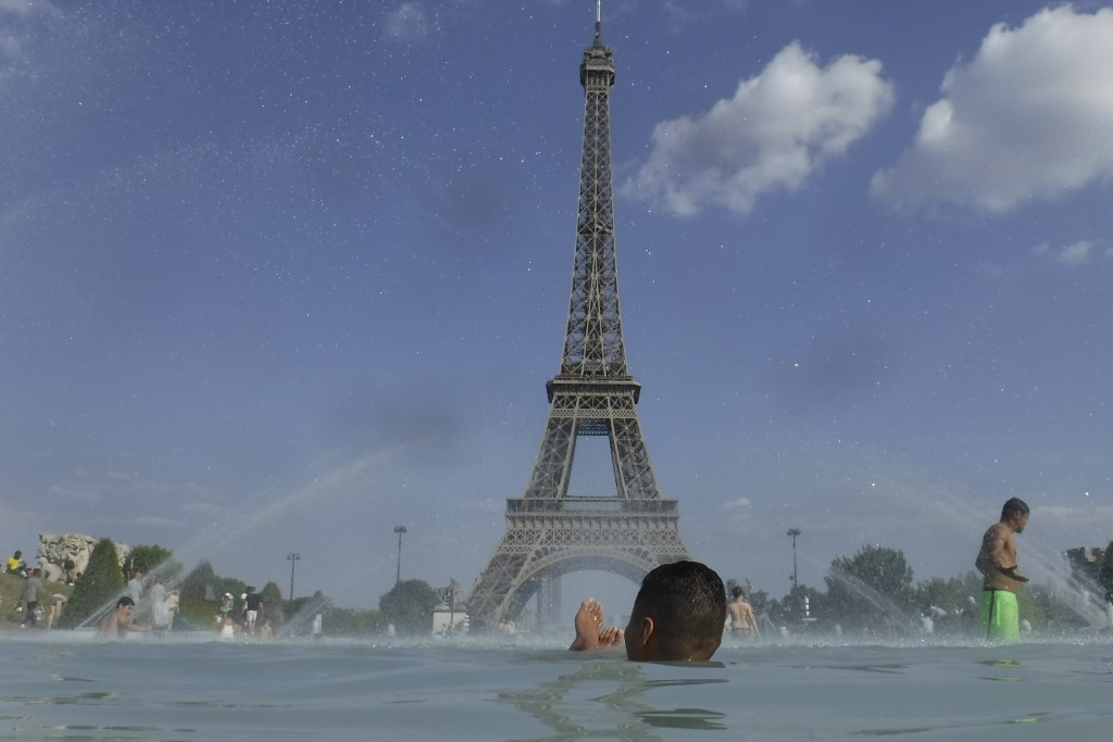 People cool off in the fountain of the Trocadero, in Paris, Tuesday, June 25, 2019. Authorities warned that temperatures could top 40 degrees Celsius ...