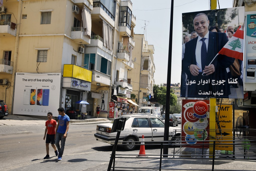 "In this Monday, June 24, 2019 photo, a poster shows George Aoun, head of the municipality of the village of Hadat, with Arabic that reads ""We are all ..."
