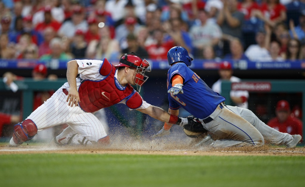 Philadelphia Phillies catcher J.T. Realmuto, left, tags out New York Mets' Jeff McNeil at home plate on a ball hit by Pete Alonso during the fourth in...