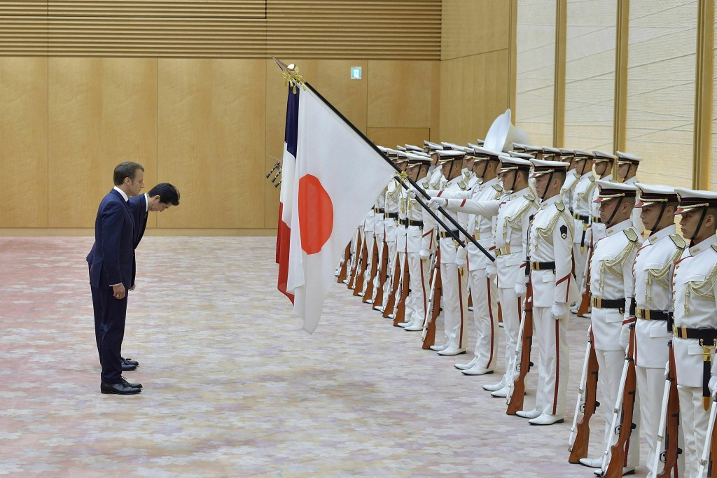 French President Emmanuel Macron, rear, and Japanese Prime Minister Shinzo Abe review an honor guard prior to their meeting at Abe's official residenc...