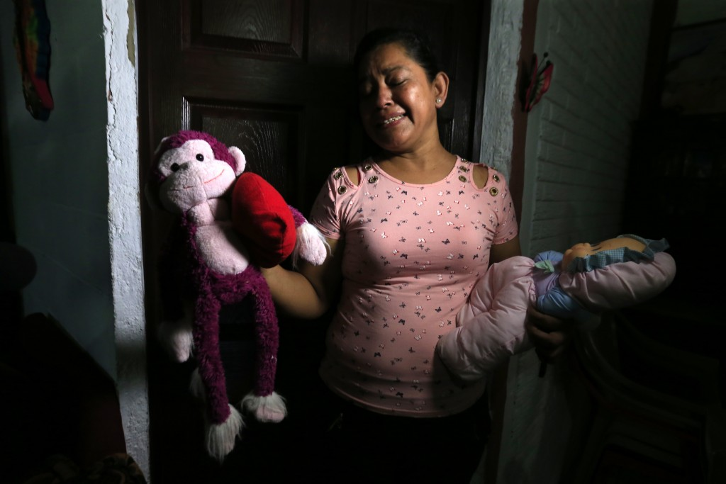 Rosa Ramirez sobs as she shows journalists toys that belonged to her nearly 2-year-old granddaughter Valeria in her home in San Martin, El Salvador, T...