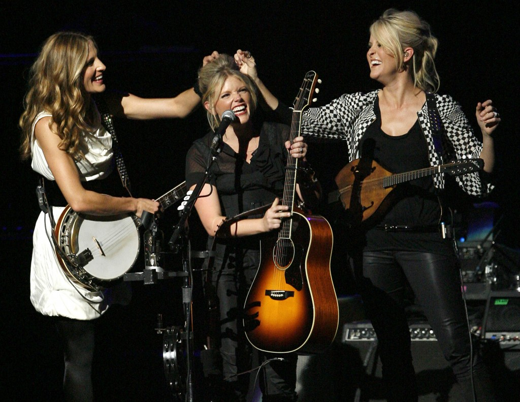 FILE - In this Oct. 18, 2007 file photo, Emily Robison, left, and Martie Maguire, right, adjust Natalie Maines' hair as the Dixie Chicks perform at th...