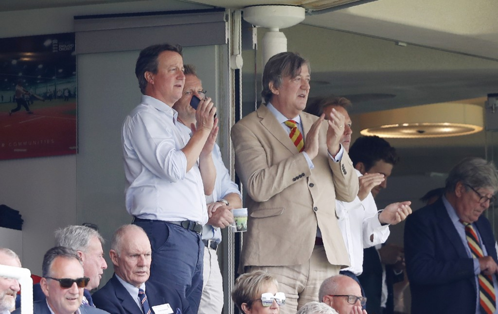 Former British Prime Minister David Cameron, left with TV personality and writer Stephen Fry watch the Cricket World Cup match between England and Aus...