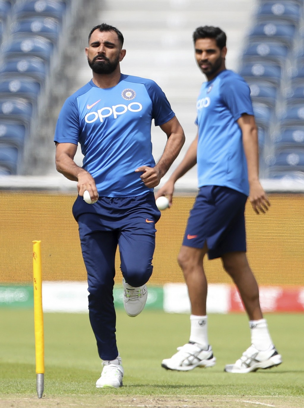 India's Bhuvneshwar Kumar, right, watches fellow bowler Mohammed Shami bowl during a training session ahead of their Cricket World Cup match against W...