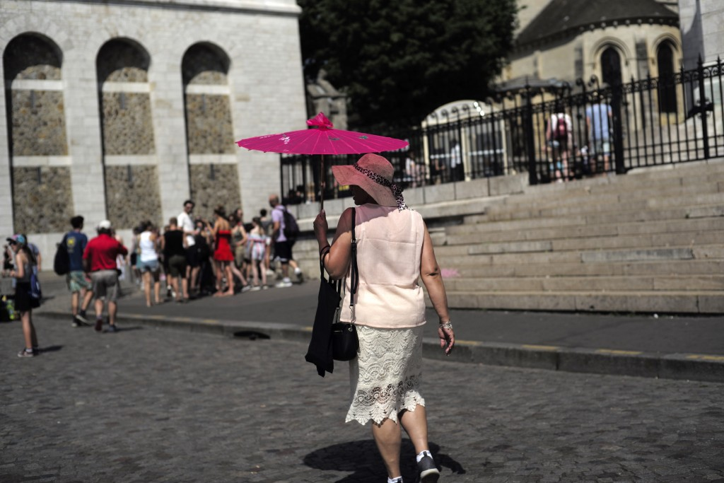 A tourist shelters under an umbrella Wednesday, June 26, 2019 in the Montmartre district of Paris. More than half of France is on alert for high tempe...