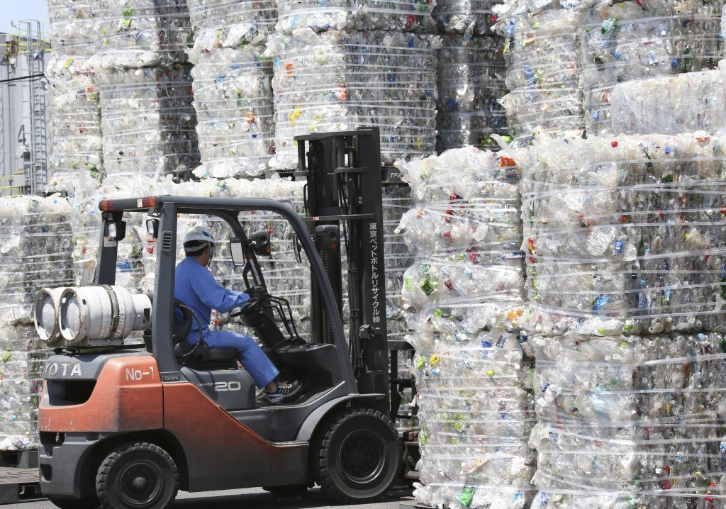In this June 18, 2019, photo, a plastic recycling company worker on a forklift truck moves a pile of plastic bottles collected for processing at Tokyo