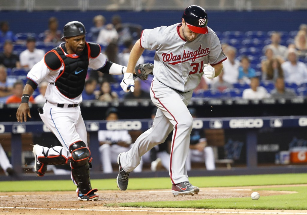 Washington Nationals' Max Scherzer (31) heads to first with a bunt single as Miami Marlins catcher Wilkin Castillo runs after the ball during the four...