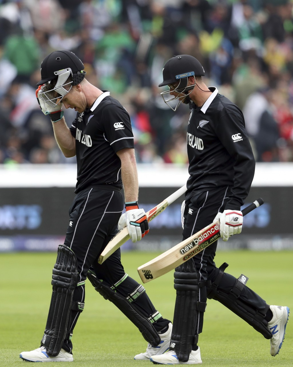 New Zealand's batsman James Neesham, left, with teammate Mitchell Santner leave the crease at the end of their innings during the Cricket World Cup ma...