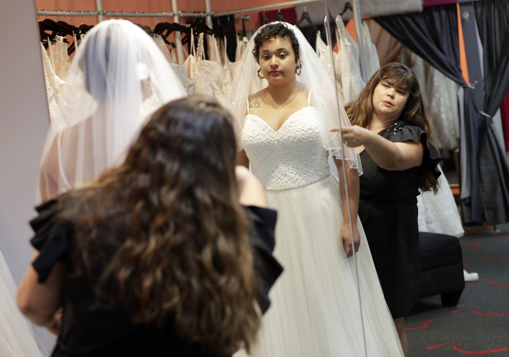 In this Friday, June 21, 2019, photo Ann Campeau,, right, owner of Strut Bridal, fits a new dress on inventory manager Stefanie Zuniga at her shop in ...