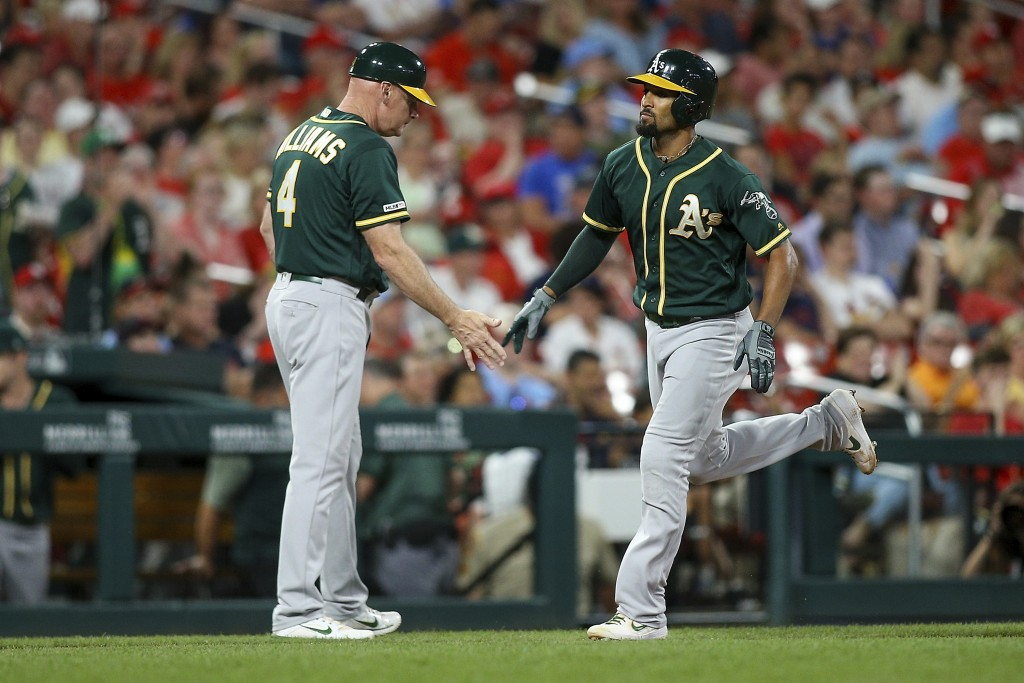 Marcus Semien, right, is congratulated by third base coach Matt Williams (4) as he runs the bases after hitting a solo home run during the fifth innin...