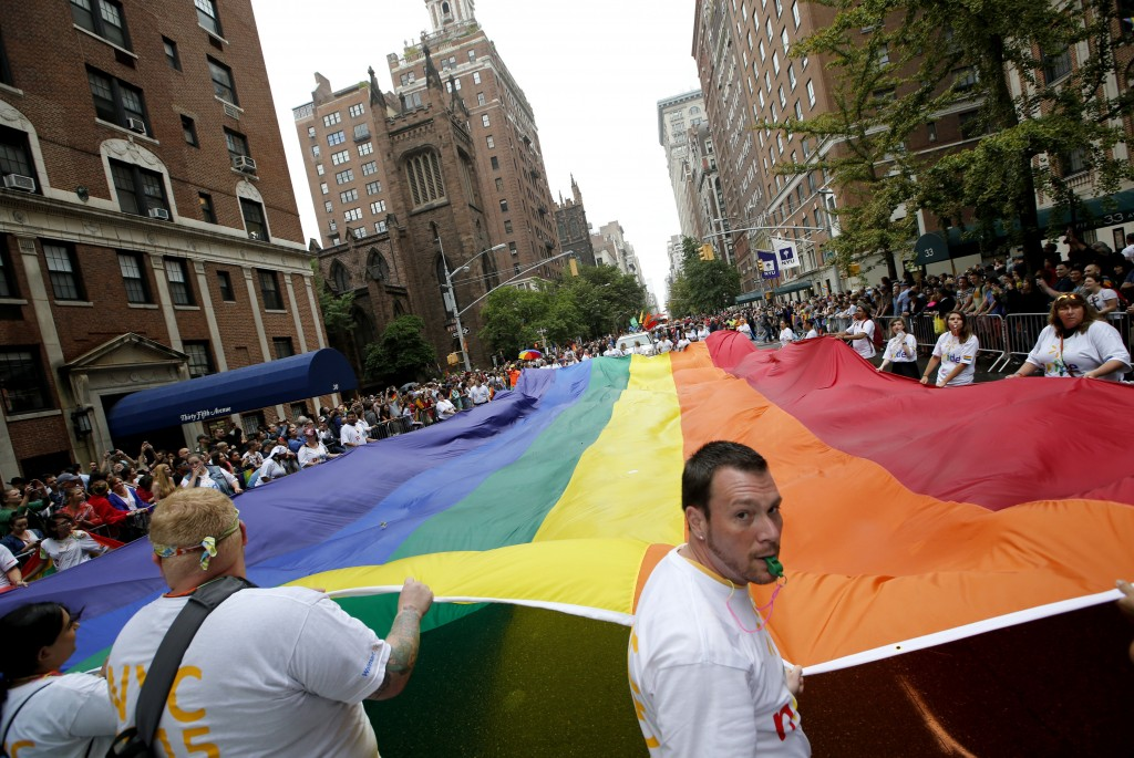 In this June 28, 2015 file photo, participants carry a rainbow-colored flag down Fifth Avenue in New York during the Heritage Pride March in New York....