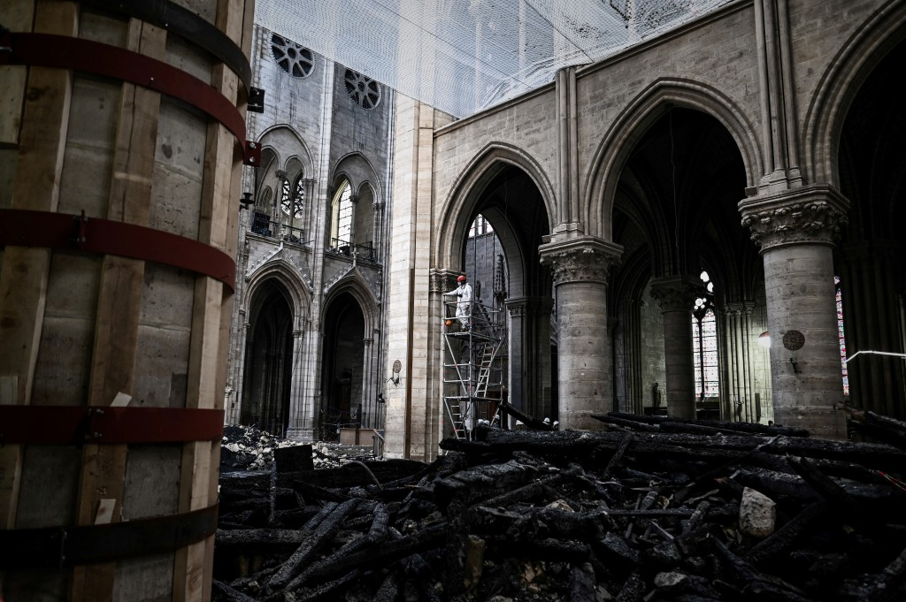 FILE - In this May 15, 2019 file photo, a worker stands on scaffolding during preliminary work inside the Notre Dame de Paris Cathedral. The Paris pro