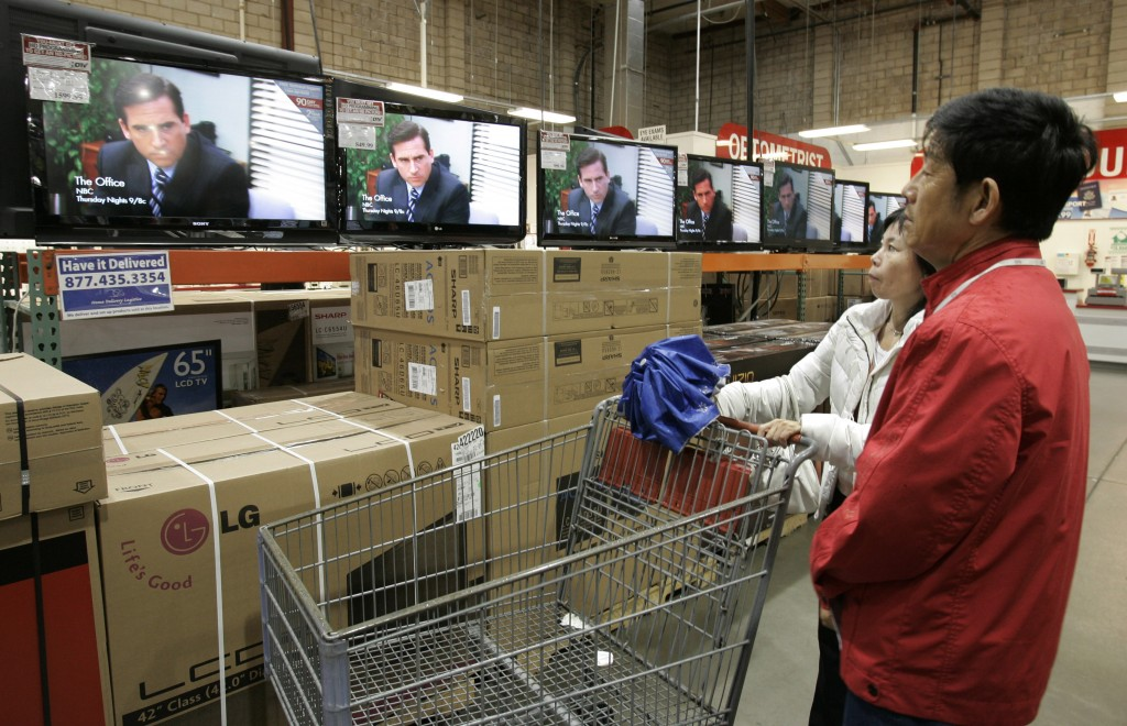 "FILE - In this Feb. 22, 2009, file photo shoppers watch the television show ""The Office"" as they compare wide screens on display at Costco in Mountain"