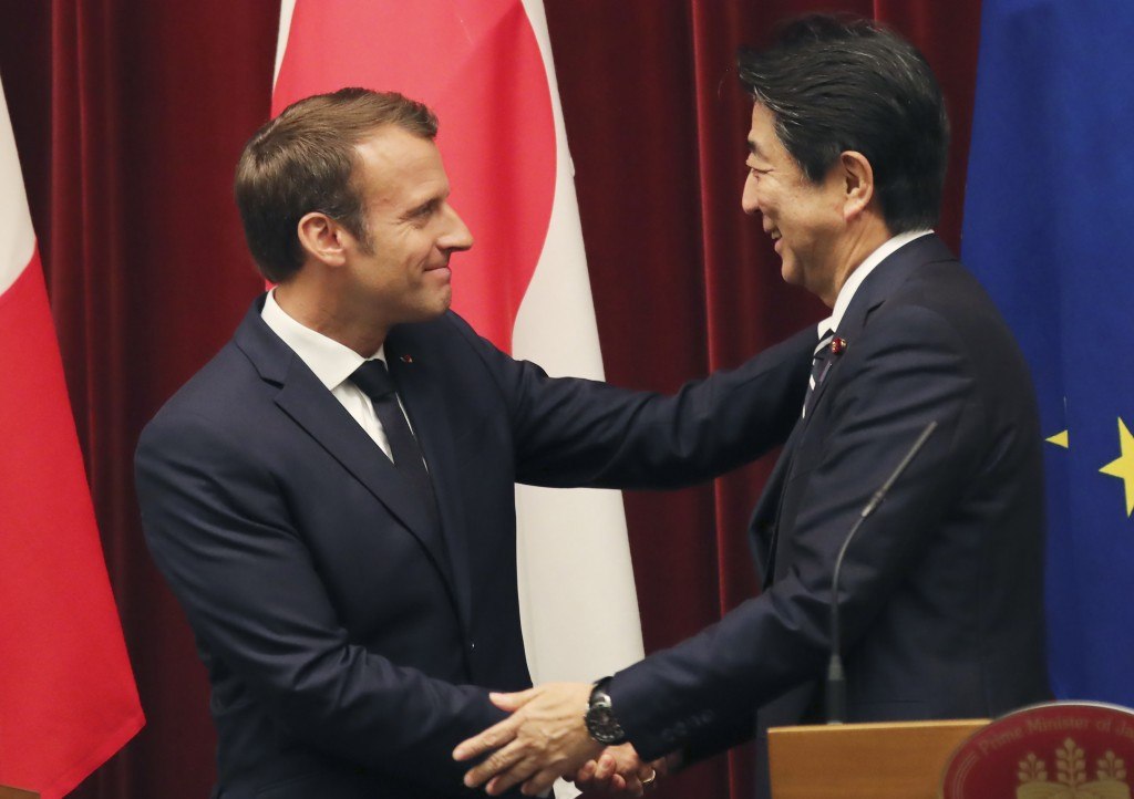 French President Emmanuel Macron, left, shakes hands with Japanese Prime Minister Shinzo Abe after their joint press conference at Abe's official resi...