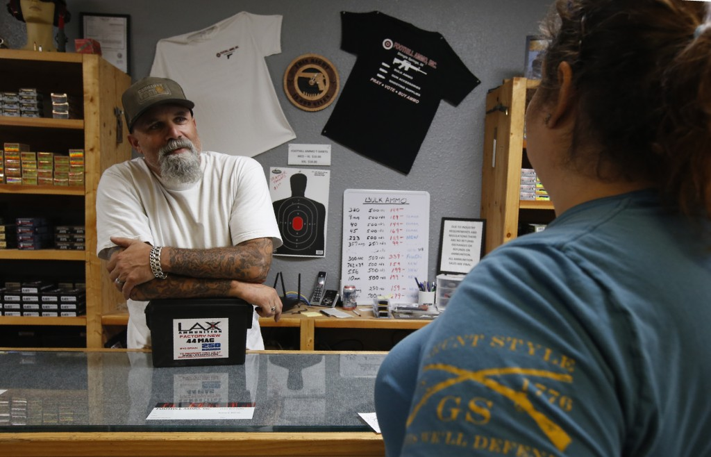 In this photo taken Tuesday, June 11, 2019, Chris Puehse, left owner of Foothill Ammo helps a customer at his shop in Shingle Springs, Calif. Californ