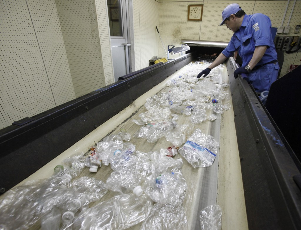 In this June 18, 2019, photo, a plastic recycling company worker makes hand sorting on plastic bottles at Tokyo Petbottle Recycle Co., in Tokyo. Japan