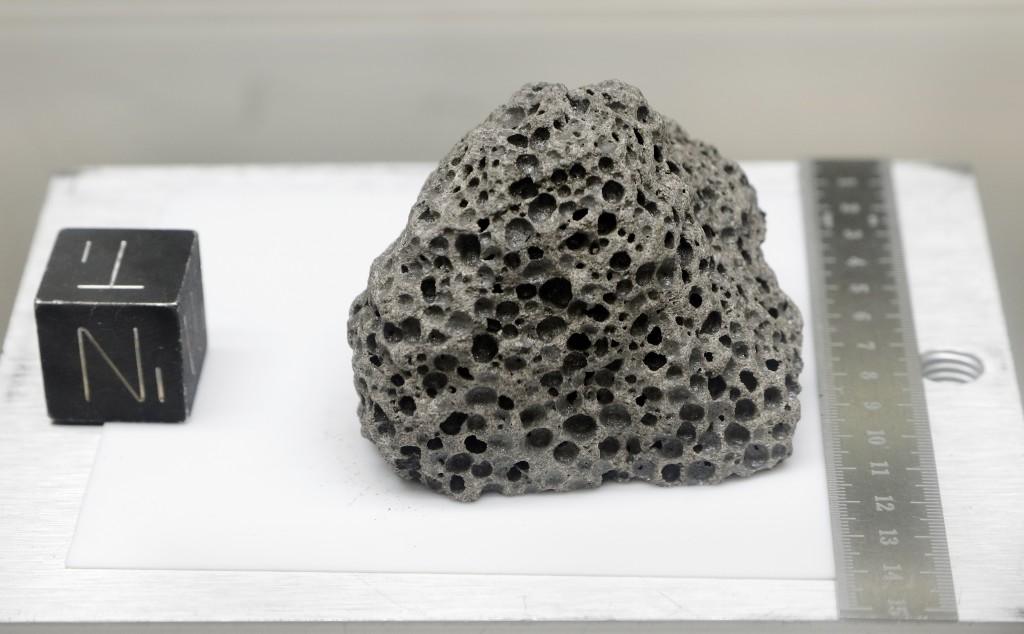 Collected during Apollo 15, a 3.5 billion years old basalt rock similar to rocks formed around Hawaii, is displayed in a pressurized nitrogen-filled e...
