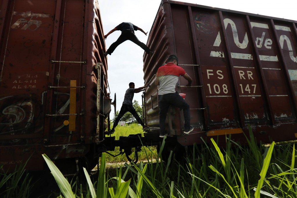 Migrants catch a ride on a freight train on their way north, in Salto del Agua, Chiapas state, Mexico, Tuesday, June 25, 2019. The group's next stop w...