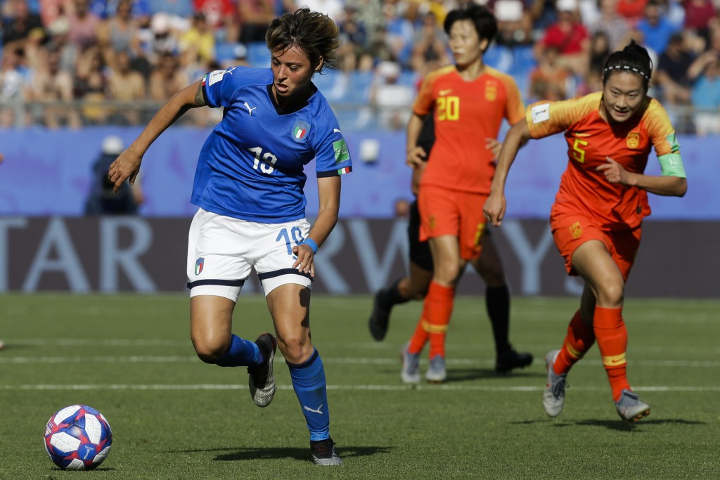 Italy's Valentina Giacinti, left, runs with the ball next to China defenders during the Women's World Cup round of 16 soccer match between Italy and C...