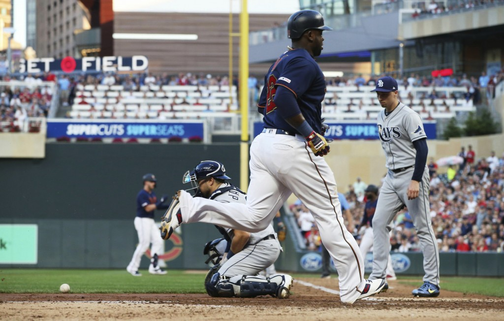 Minnesota Twins' Miguel Sano scores on a two-run single by Mitch Garver as Tampa Bay Rays catcher Austin Meadows, left, waits for the throw and pitche...