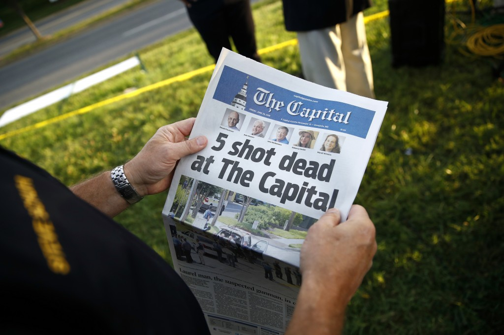 FILE - In this June 29, 2018, file photo, Steve Schuh, county executive of Anne Arundel County, holds a copy of the Capital Gazette near the scene of ...