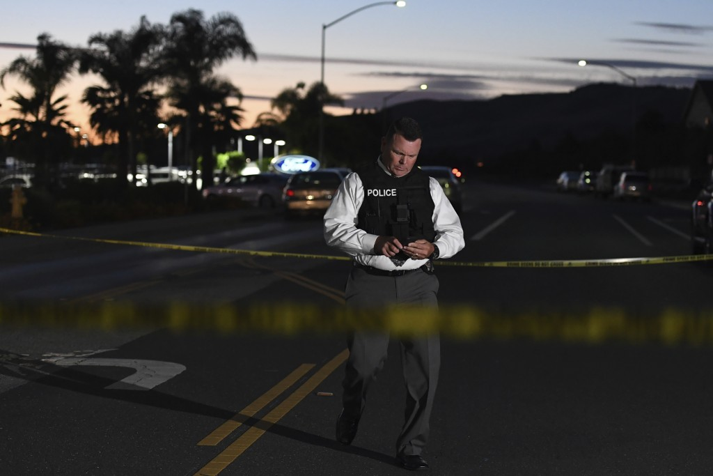 Morgan Hill Police Sgt. Bill Norman walks down Condit Avenue near a Ford dealership in Morgan Hill, Calif., after a fatal shooting Tuesday, June 25, 2...