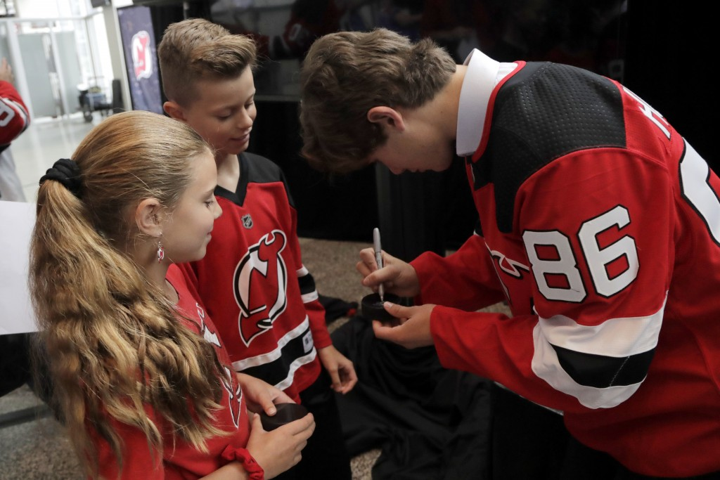 New Jersey Devils forward Jack Hughes, right, the No. 1 overall pick in the 2019 NHL hockey draft, signs autographs for Nicholas Palumbo, 12, center, ...