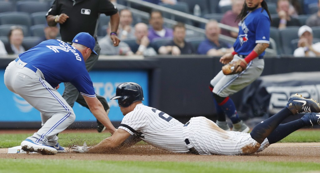 Toronto Blue Jays starting pitcher Clayton Richard, left, tags out New York Yankees' Giancarlo Stanton at third during the first inning of a baseball ...
