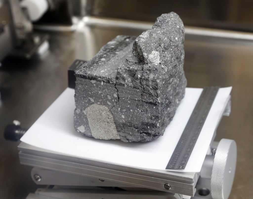 A regolith breccia rock of sintered lunar soil, dating 3.2 billion years old and collected by Apollo 15, is displayed in a pressurized nitrogen-filled...