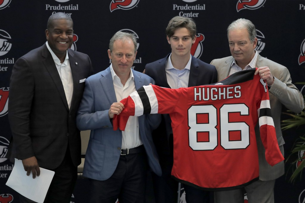 New Jersey Devils forward Jack Hughes, center right, the No. 1 overall pick in the 2019 NHL draft, poses for photographers with former NHL player Kevi...