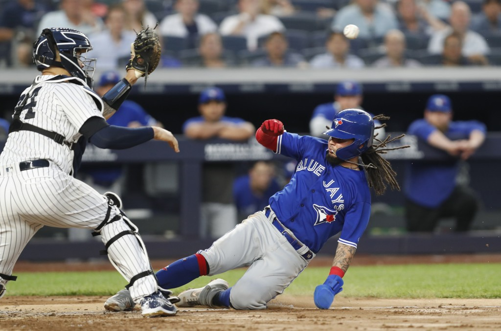 New York Yankees catcher Gary Sanchez, left, waits for the throw as Toronto Blue Jays' Freddy Galvis slides in to score on Eric Sogard's sacrifice fly...