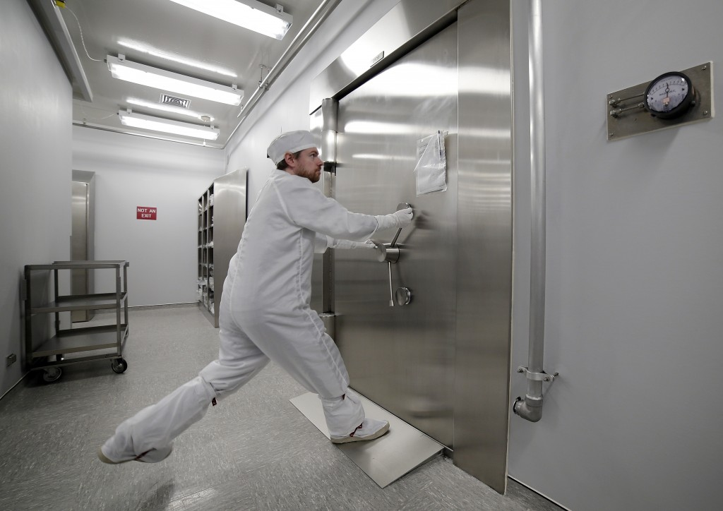 Jeremy Kent, Apollo sample curation processor, tugs to open the 1978 U.S. federal bank vault that protects the entrance to the lunar sample vault insi...