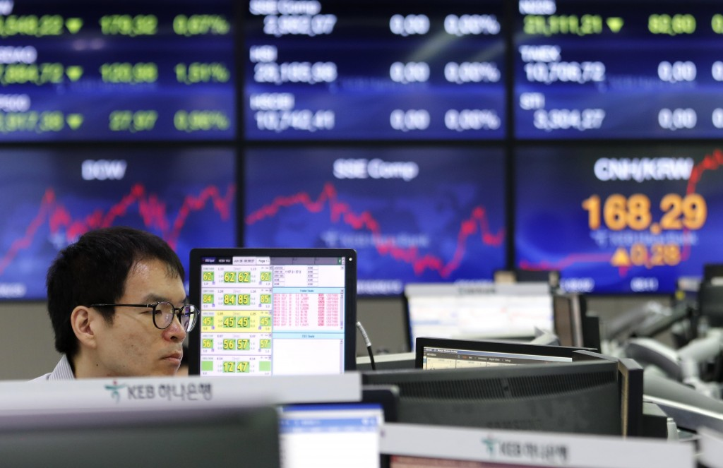 A currency trader watches monitors at the foreign exchange dealing room of the KEB Hana Bank headquarters in Seoul, South Korea, Wednesday, June 26, 2...