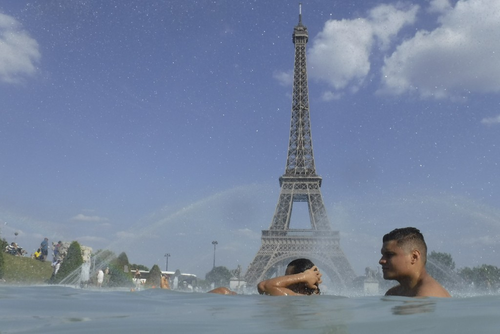 People cool off in the fountain of the Trocadero, as the Eiffel Tower is visible in background, in Paris, Tuesday, June 25, 2019. Authorities warned t...