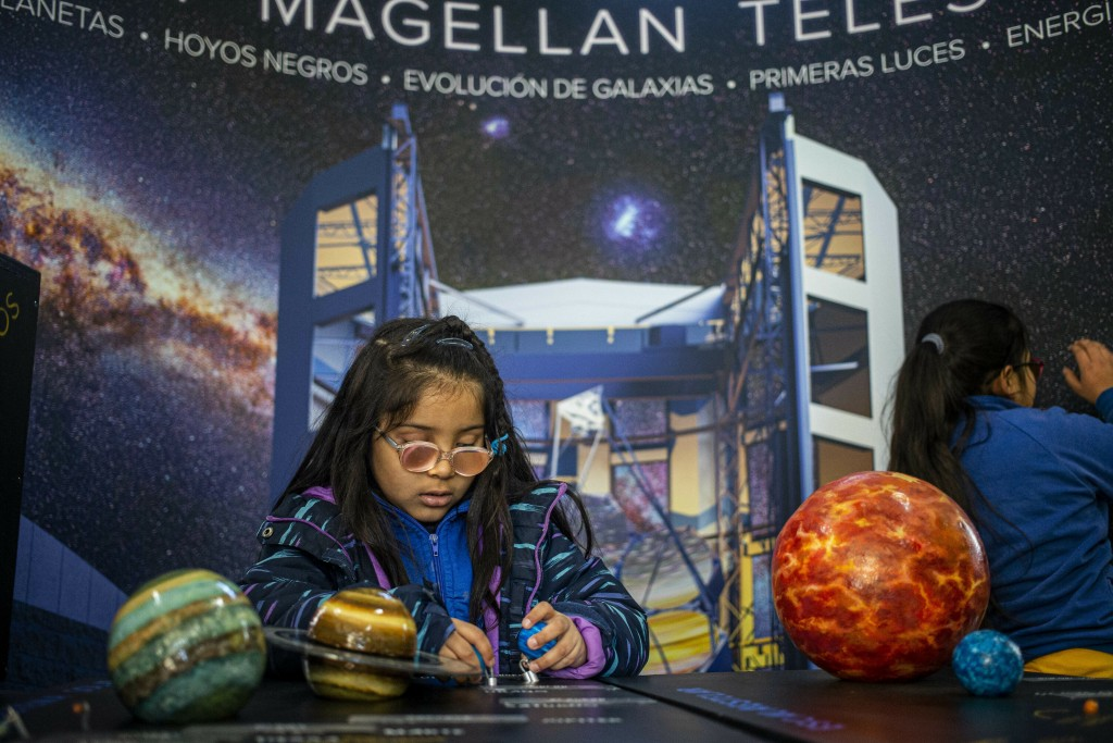 A blind child interacts with a representation of the solar system during sensorial experience with tools created by NASA and Edinburgh University to e...