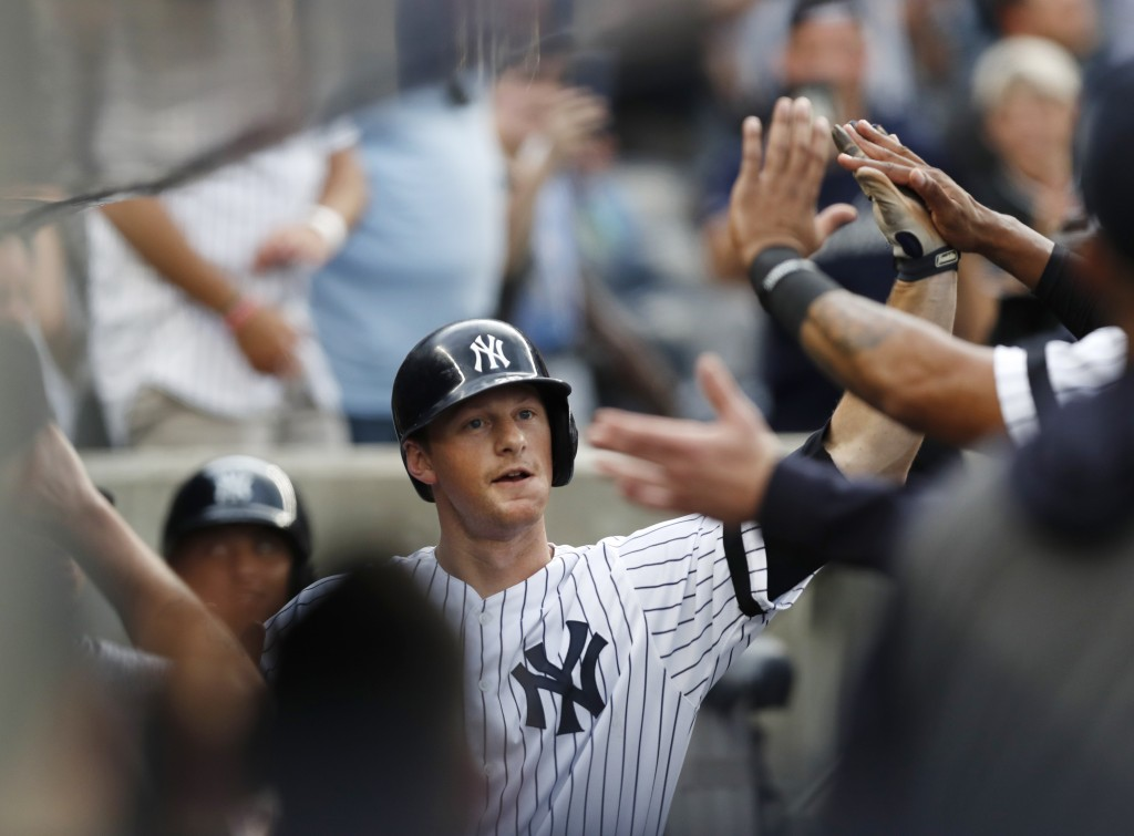New York Yankees' DJ LeMahieu celebrates with teammates after hitting a solo home run during the first inning of the team's baseball game against the ...