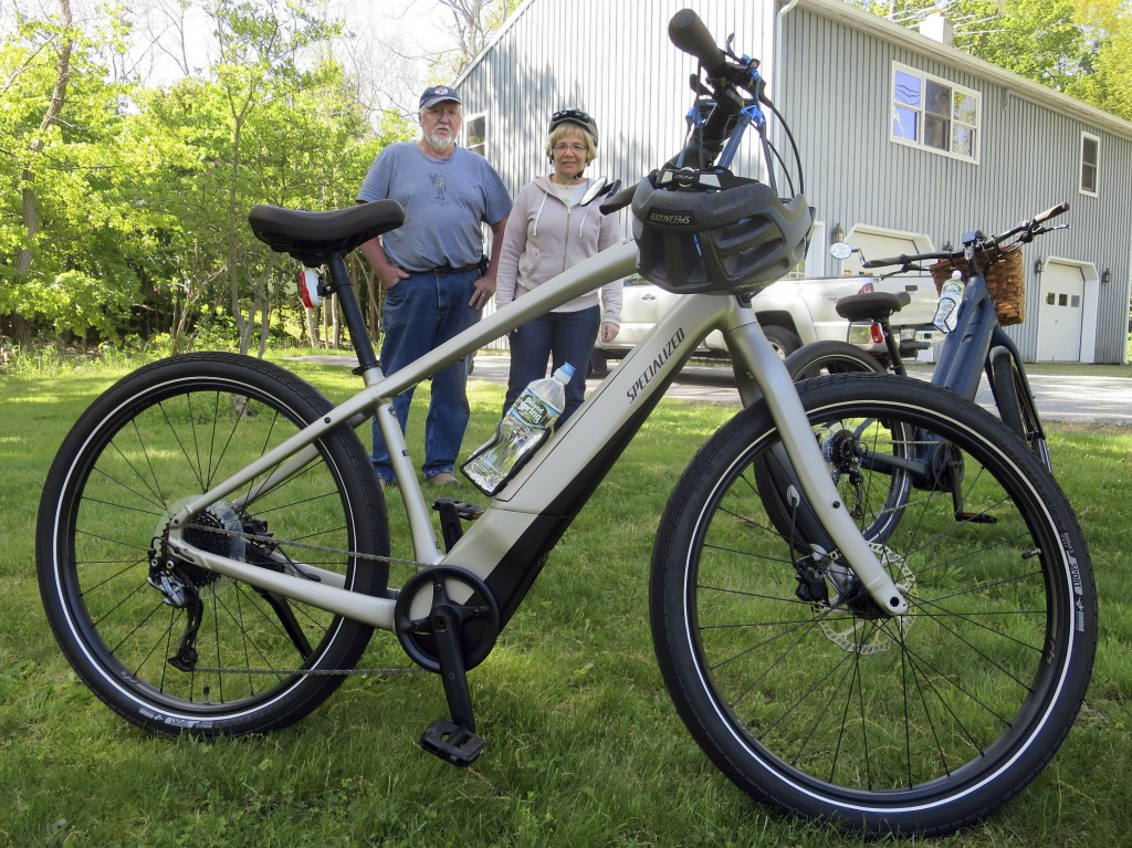 In this June 8, 2019 photo, Gordon and Janice Goodwin show their electric-assist bicycles outside their home in Bar Harbor, Maine. The bikes are banne...