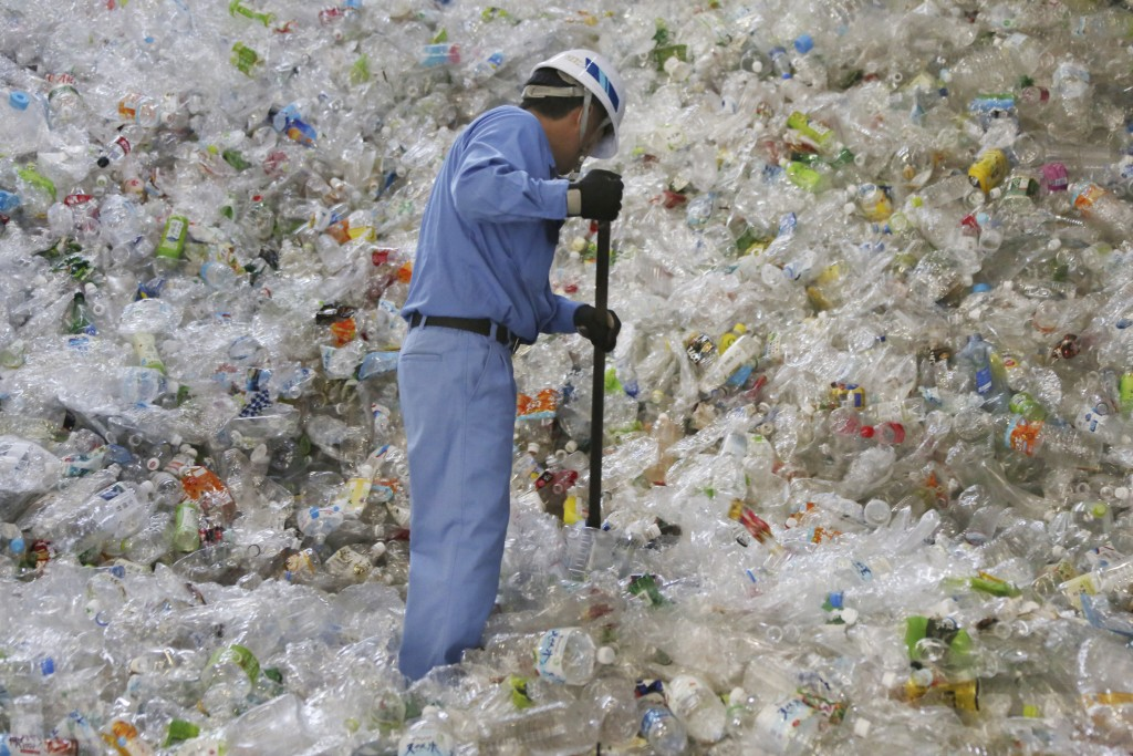 In this June 18, 2019, file photo, a plastic recycling company worker sorts out plastic bottles collected for processing at Tokyo Petbottle Recycle Co...